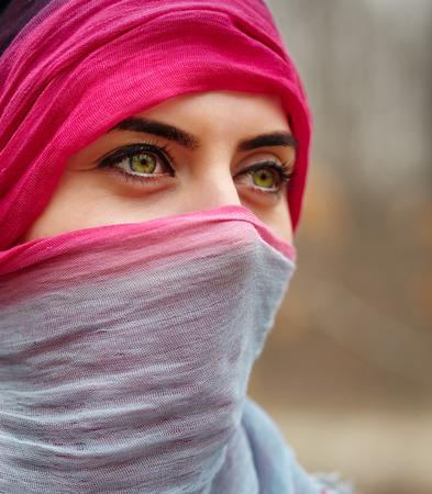 아름다운 녹색 눈을 가진 회교도 여자의 근접 촬영 초상화 스톡 콘텐츠