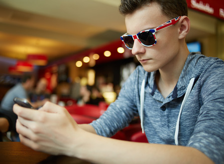 Teenager boy with sunglasses sitting in a restaurant and playing on a smartphone photo