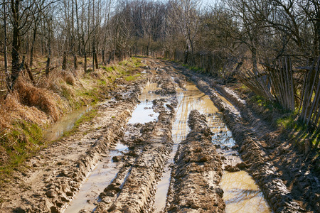 muddy tracks: Muddy wet countryside road with weel tracks filled with dirty water Stock Photo