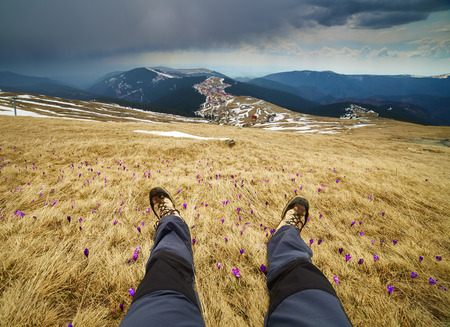 extreme angle: Wide view with legs of a man resting on a peak of high mountains
