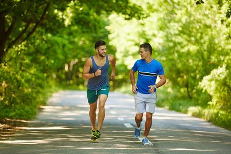 personas trotando: Dos amigos que se ejecutan a través del bosque en una pista de jogging Foto de archivo