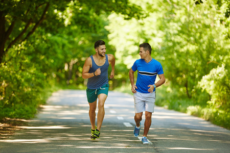 jogging in nature: Two friends running through the forest on a jogging trail