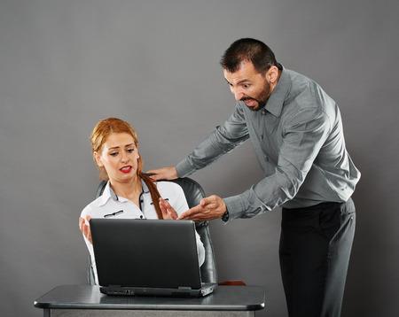 jefe enojado: Protuberancia enojada que grita en su empleado mujer de m�s de un error que hizo en su computadora port�til