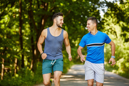 Two friends running through the forest on a jogging trail photo
