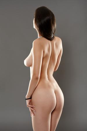 Vista trasera de una mujer desnuda sobre fondo gris