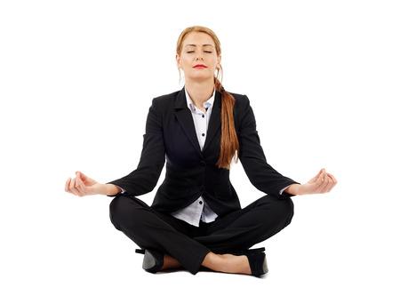 ヨガは、白で隔離の蓮華座に座っている美しい女性実業家
