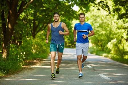 young man: Two friends running through the forest on a jogging trail