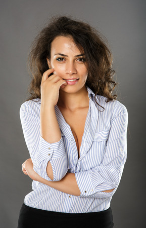 contemplative: Contemplative young hispanic businesswoman on gray background, closeup Stock Photo