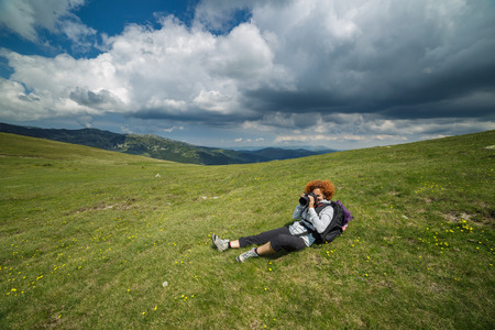 profesional: Woman hiker taking pictures with profesional camera on a mountain meadow Stock Photo