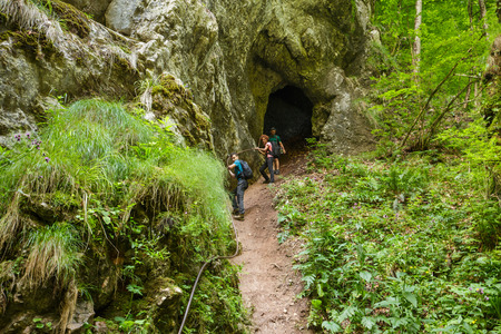 getting out: Family of hikers getting out from a cave holding on to a safety cable