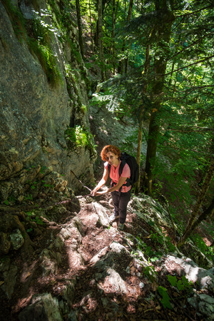 climbing cable: Woman with backpack climbing on safety cable on a wall in the forest Stock Photo