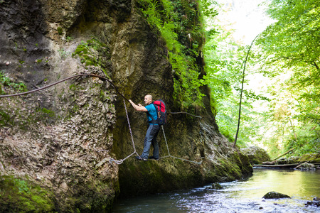 perilous: Caucasian backpacker traversing a perilous side of a wall on safety cables, over a river