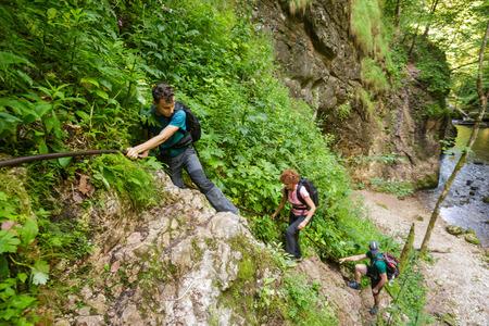 Familia de excursionistas escalada en cables de seguridad en un cañón Foto de archivo - 43207902