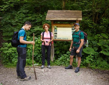 information point: Family of hikers standing in the forest near an information point Stock Photo