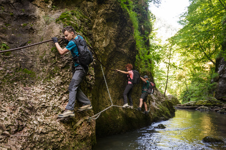 Family of hikers climbing on safety cables in a gorge above the river Foto de archivo