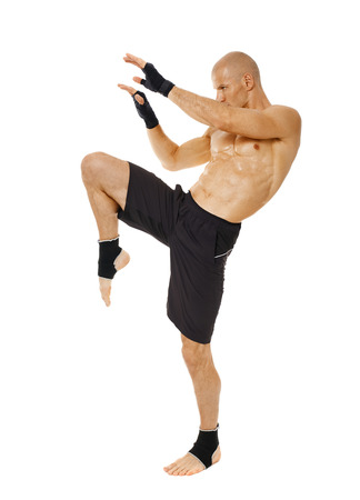 kickboxing: Muay thai fighter delivering a knee blow, isolated on white background