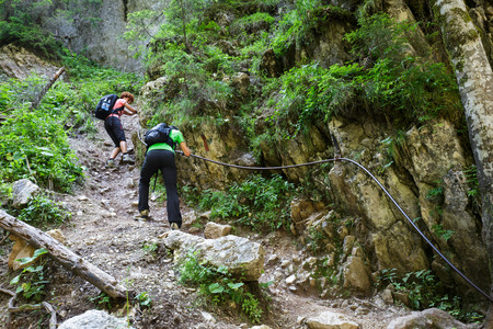 climbing cable: Family of hikers climbing on a safety cable on a very steep trail Stock Photo