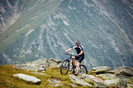 Mountain bike cyclist in sport equipment and helmet riding on rugged trails