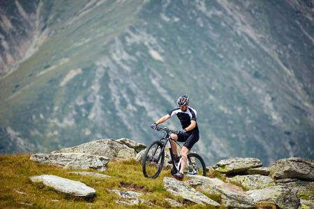 ciclista: Ciclista de la bici de montaña en el equipamiento deportivo y paseos casco en caminos accidentados