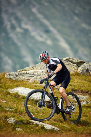 bicycle race: Mountain bike cyclist in sport equipment and helmet riding on rugged trails