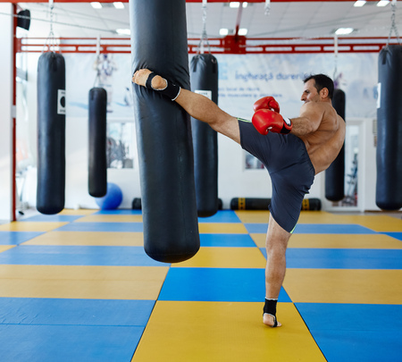 gym: Kickbox fighter training in the gym with the punch bag