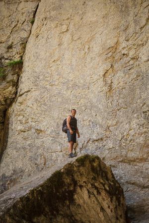 large rock: Caucasian hiker standing on a large rock at the entrance of a cave
