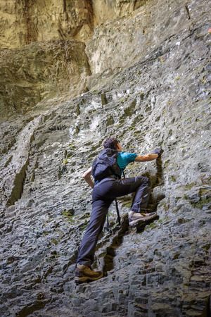 free climbing: Teenage boy doing free climbing on a very steep wall