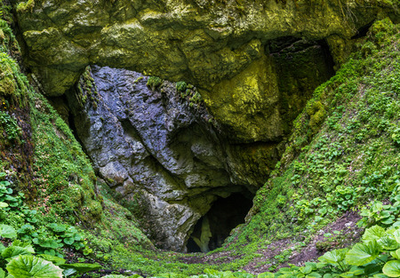 cave exploring: Mountain landscape with a very large sinkhole entrance