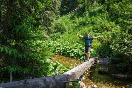 river trunk: Happy male hiker crossing a mountain river on a huge tree trunk