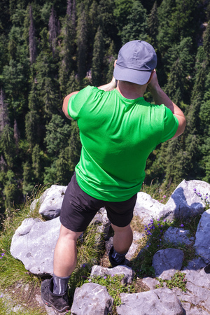 valley view: Rear view of a tourist hiker taking photos from a very high cliff