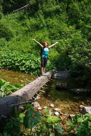 river trunk: Happy female hiker crossing a mountain river on a huge tree trunk