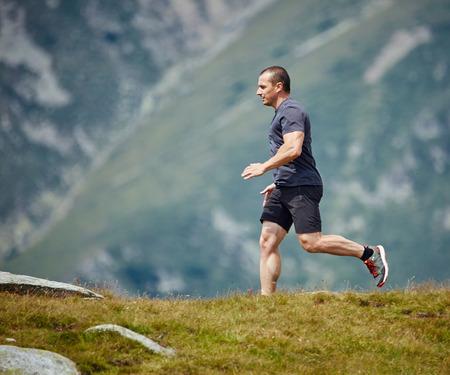 Caucasian athlete trail running in the mountains, ultramarathon