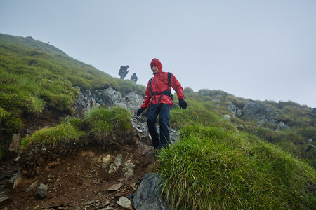 rain coat: Group of hikers descending on a mountain with raincoats during rain