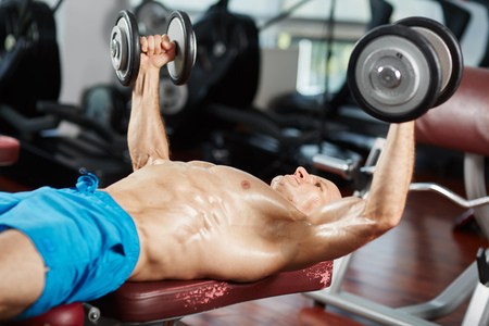 dumbbell: Young fit man working out at bench press with dumbbells