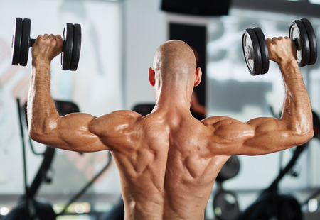 deltoids: Muscular athlete shirtless doing triceps and shoulder workout with dumbbells