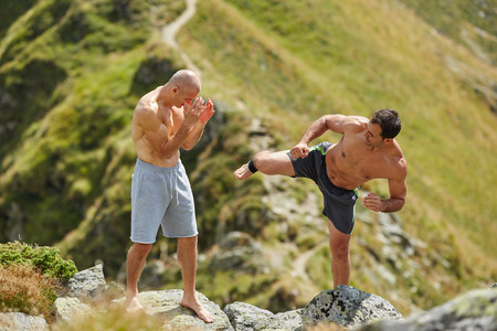 thai people: Kickboxers or muay thai fighters training in the mountains, sparring