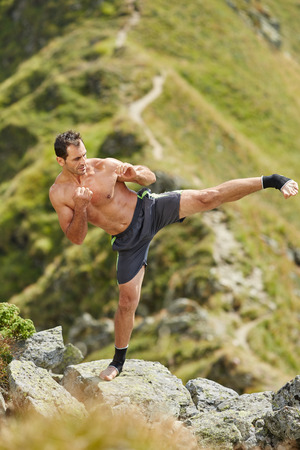 outdoor training: Kickboxer or muay thai fighter practicing shadow boxing on a mountain Stock Photo