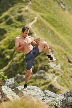kickboxer: Kickboxer or muay thai fighter practicing shadow boxing on a mountain Stock Photo