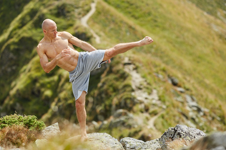aggressive people: Kickboxer or muay thai fighter practicing shadow boxing on a mountain Stock Photo