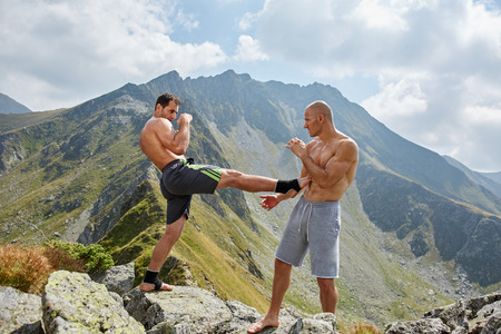 outdoor training: Kickboxers or muay thai fighters training in the mountains, sparring