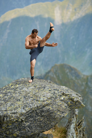 muay: Kickboxer or muay thai fighter practicing shadow boxing on a mountain cliff