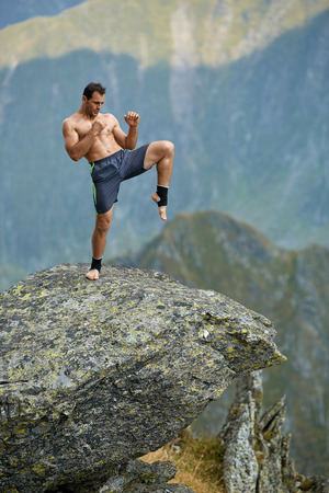 thai boxing: Kickboxer or muay thai fighter practicing shadow boxing on a mountain cliff