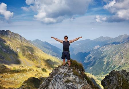 Heureux homme aux bras levés debout sur une falaise de montagne en appréciant la liberté
