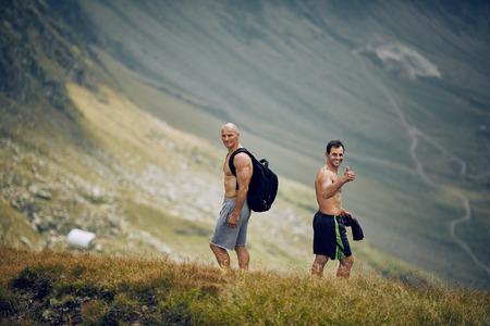 hombres sin camisa: Dos hombres sin camisa de excursión en rastro de montaña