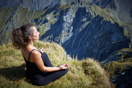 one female: Young beautiful woman yoga meditating  and relaxing on the top of a mountain at sunrise Stock Photo