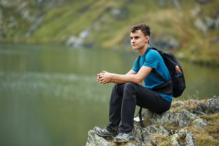 gente sentada: Muchacho del caminante con mochila por el lago en las monta�as Foto de archivo