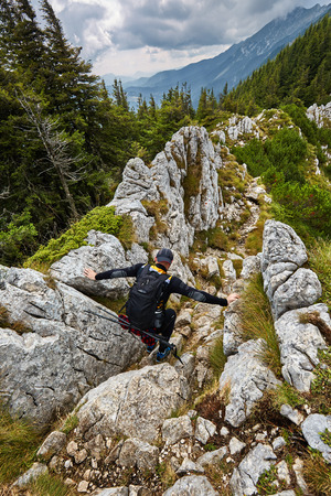 risk free: Hiker man climbing on a difficult mountain trail
