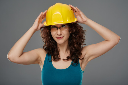 head protection: Young female engineer putting a protection helmet on her head Stock Photo
