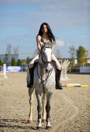 hippodrome: Beautiful young woman riding a horse on a hippodrome Stock Photo