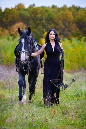 sexy young girl: Красивая женщина с черной лошади и арбалета прогулки в лесу, концепция фантазии